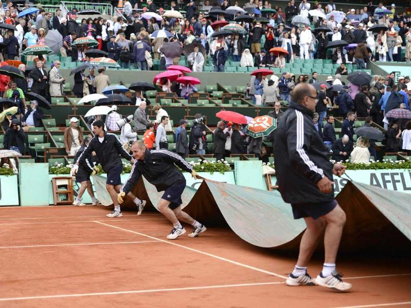 Staff members cover the Philippe Chatrier court from rain after the semifinal tennis match of David Ferrer against Rafael Nadal was interrupted in Paris. AFP/Pascal Guyot