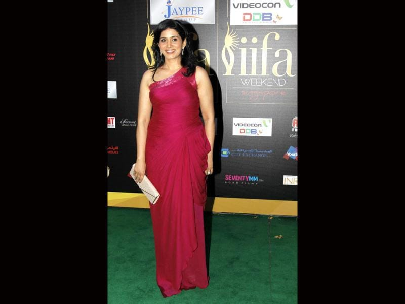 Sonali Kulkarni arrives at the green carpet in a dark pink gown.