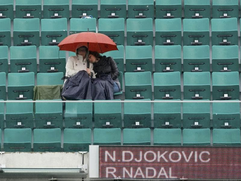 Spectators protect themselves from the rain with umbrella as rain stops the men's singles final match between Rafael Nadal of Spain and Novak Djokovic of Serbia during the French Open tennis tournament at the Roland Garros stadium in Paris Reuters/Benoit Tessier