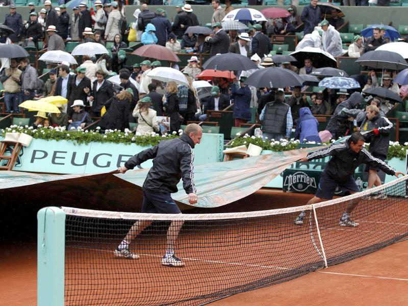 Grounds staff cover the court as rain stops the men's singles final match between Rafael Nadal of Spain and Novak Djokovic of Serbia during the French Open tennis tournament at the Roland Garros stadium in Paris Reuters/Gonzalo Fuentes