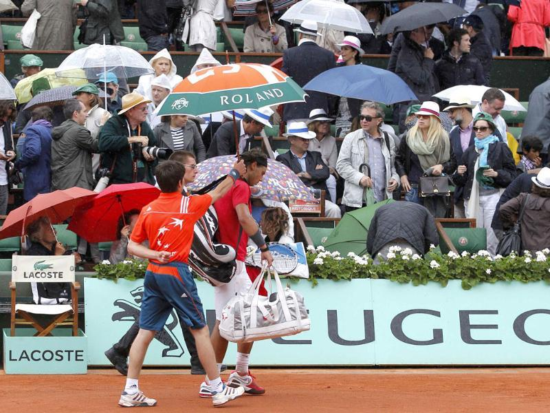 Rafael Nadal of Spain leaves the court under an umbrella as rain stops the play during his men's singles final match against Novak Djokovic of Serbia at the French Open tennis tournament at the Roland Garros stadium in Paris Reuters/Gonzalo Fuentes