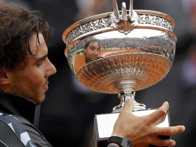 Rafael Nadal of Spain holds the trophy as he poses during the ceremony after defeating Novak Djokovic of Serbia during their men's singles final match at the French Open tennis tournament at the Roland Garros stadium in Paris. Reuters Photo/Benoit Tessier
