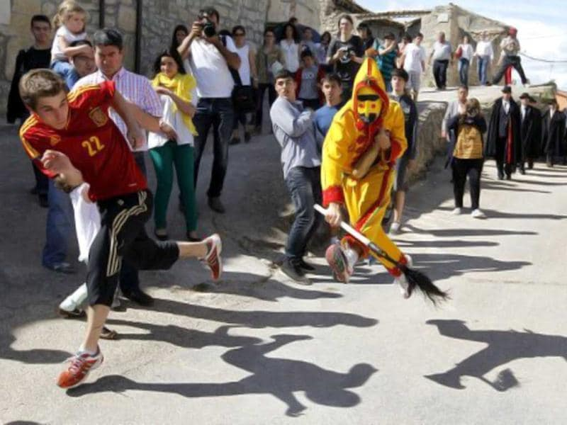 A man dressed up as the devil chases children during 'El Colacho', the 'baby jumping festival' in the village of Castrillo de Murcia, near Burgos. Baby jumping (El Colacho) is a traditional Spanish practice dating back to 1620 that takes place annually to celebrate the Catholic feast of Corpus Christi. During the act - known as El Salto del Colacho (the devil's jump) or simply El Colacho - men dressed as the Devil jump over babies born the last twelve months of the year who lie on mattresses in the street. AFP Photo / Cesar Manso