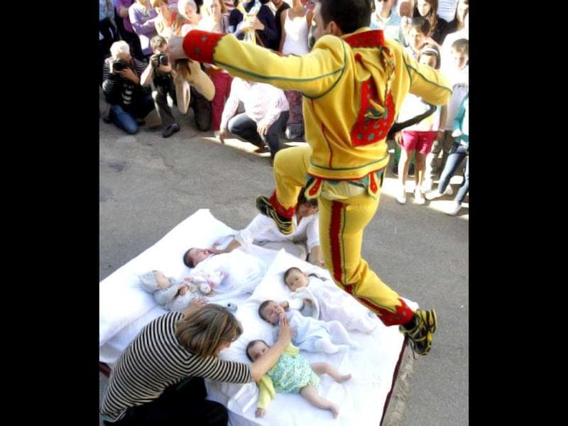 A man dressed up as the devil jumps over babies lying on a mattress in the street during 'El Colacho', the 'baby jumping festival' in the village of Castrillo de Murcia, near Burgos. Baby jumping (El Colacho) is a traditional Spanish practice dating back to 1620 that takes place annually to celebrate the Catholic feast of Corpus Christi. AFP Photo / Cesar Manso