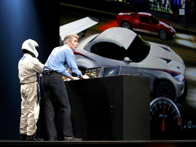 Craig Federighi, Apple Senior Vice President, Software Engineering, with a man in a racing suit, demonstrates Racer OS X during the Apple Worldwide Developers Conference 2012 in San Francisco, California June 11, 2012. REUTERS/Stephen Lam