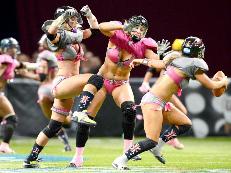 Western conference player Chloe Butler (C) attempts to tackle Eastern Conference player KK Mathney (R) as Kyle DeHaven (L) blocks during their Lingerie Football League (LFL) All-Stars match in Sydney. AFP Photo/William West
