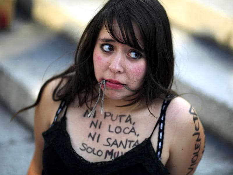 A woman pretends to be gagged while taking part in a protest during International Women's Day in Mexico City. The writing on the woman's chest reads,