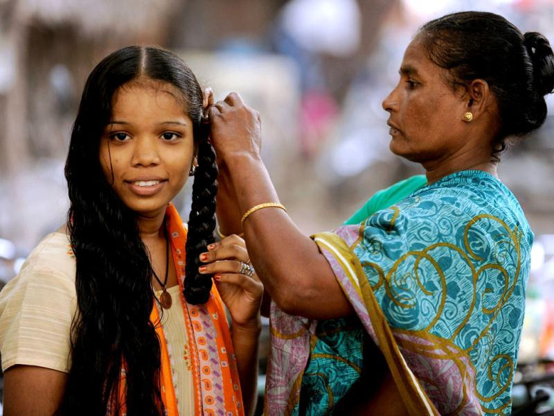 A young woman has her wet hair braided by her mother in Chennai. Reuters files/Philip Brown