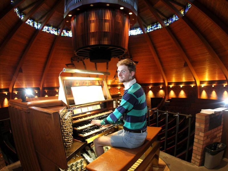 Organist Christopher Keady sits at the circular pipe organ at the Agnes Flanagan Chapel Tuesday, June 12, 2012, on the campus of Lewis ' + char(38) +' Clark College, in Portland, Ore. The Agnes Flanagan Chapel is a 16-sided architectural marvel that seats 650 under stained glass windows depicting the book of Genesis. In the early 1970s, it was also a big, conical quandary. Chapels aren't really chapels unless they have an organ, and the newly-minted structure at Portland's Lewis ' + char(38) +' Clark College was in need. (AP Photo/Rick Bowmer)