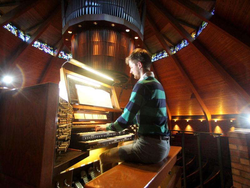 Organist Christopher Keady plays the circular pipe organ at the Agnes Flanagan Chapel Tuesday, June 12, 2012, on the campus of Lewis ' + char(38) +' Clark College, in Portland, Ore. The Agnes Flanagan Chapel is a 16-sided architectural marvel that seats 650 under stained glass windows depicting the book of Genesis. In the early 1970s, it was also a big, conical quandary. Chapels aren't really chapels unless they have an organ, and the newly-minted structure at Portland's Lewis ' + char(38) +' Clark College was in need. (AP Photo/Rick Bowmer)