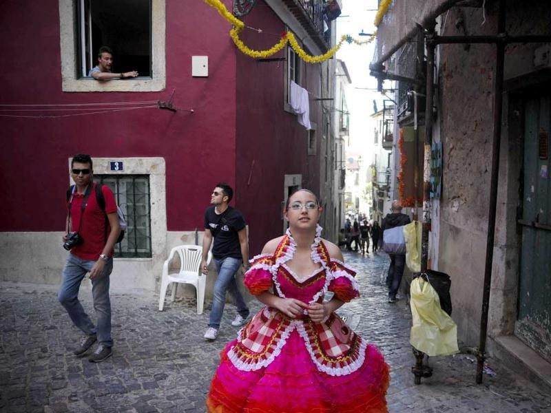 A reveler from the typical Lisbon neighborhood, Alfama, walks in costuem on her way to the Saint Anthony's Parade on Avenida da Liberdade, in Lisbon. Lisbon celebrates Saint Antony's day, its protector, with a parade that gathers participants from several typical neighborhoods of the city. AFP Photo/Patricia De Melo Moreira