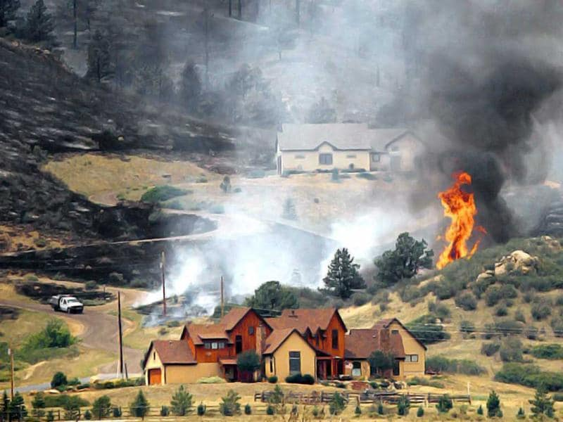 Smoke and flames encroach upon homes on the eastern front of the High Park fire near Laporte, Colorado. A wind-driven wildfire burning in the rugged Colorado canyon spread out of control, forcing hundreds of people to evacuate and one person in the fire zone was reported missing, officials said. Reuters/Marc Piscotty
