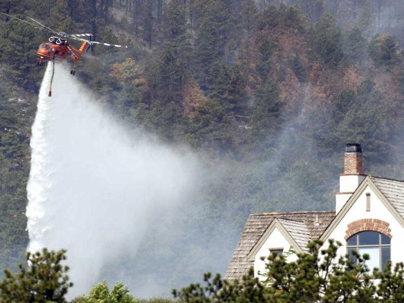 A helicopter tanker drops water near a home in Colorado's High Park Fire, about 15 miles northwest of Fort Collins. The fire was estimated to be at 37,000 acres according to the county sheriff on Monday. Reuters/Rick Wilking