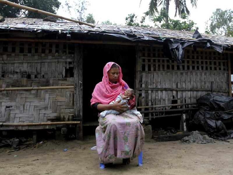A Rohingya Muslim woman who fled Myanmar to Bangladesh to escape religious violence, sits with her baby in a boat after being intercepted crossing the Naf River by Bangladesh border authorities in Taknaf, Bangladesh. AP Photo/Anurup