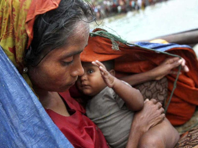 A Rohingya Muslim woman who fled Myanmar to Bangladesh to escape religious violence, sits with her baby in a boat after being intercepted crossing the Naf River by Bangladesh border authorities in Taknaf, Bangladesh. AP Photo/Anurup Titu