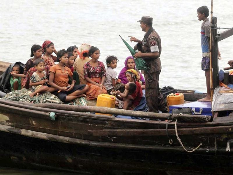 A Bangladeshi Border Police officer speaks with Rohingya Muslims who fled Myanmar to Bangladesh to escape religious violence after they were intercepted crossing the Naf River by the border authorities in Taknaf, Bangladesh. AP Photo/Anurup Titu