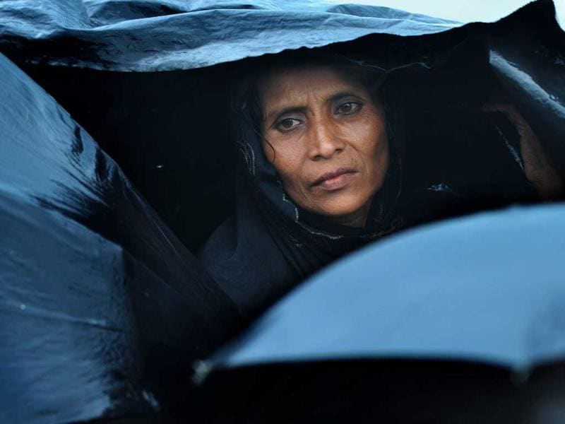 A Rohingya Muslim woman, fleeing sectarian violence in Myanmar, is pictured taking shelter under a tarp while on an intercepted boat trying to cross the Naf river into Bangladesh in Teknaf, Bangladesh. AFP Photo/ Munir uz Zaman