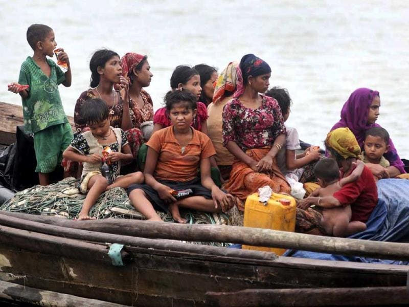 Rohingya Muslims who fled Myanmar to Bangladesh to escape religious violence, sit in a boat after they were intercepted crossing the Naf River by Bangladesh border authorities in Taknaf, Bangladesh. AP Photo/Anurup Titu