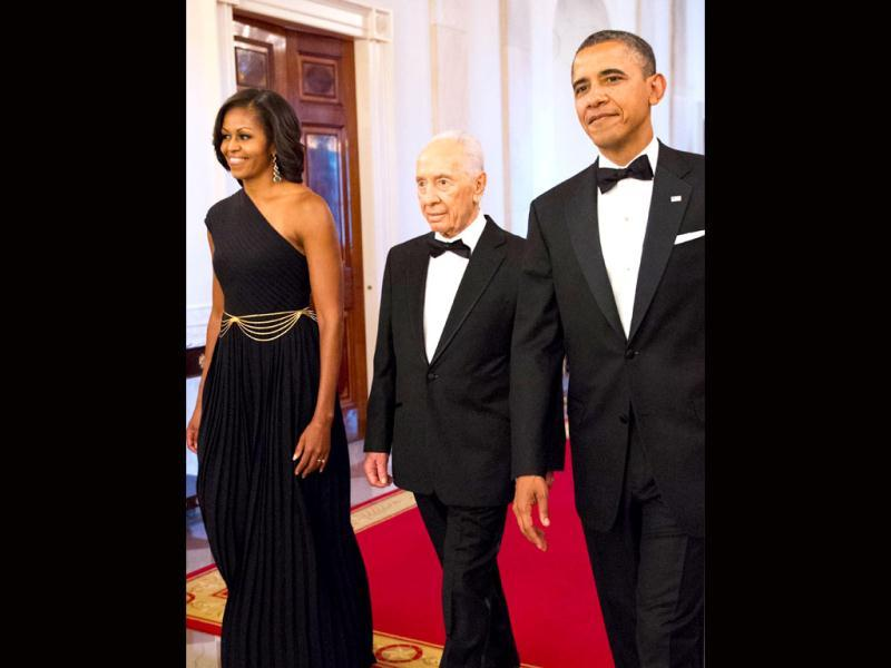 US President Barack Obama and First Lady Michelle Obama enter the East Room with Israeli President Shimon Peres for a dinner where he would be presented with the Presidential Medal of Freedom at the White House in Washington, DC. The medal is the highest civilian honour in the US. AFP/Mandel Ngan