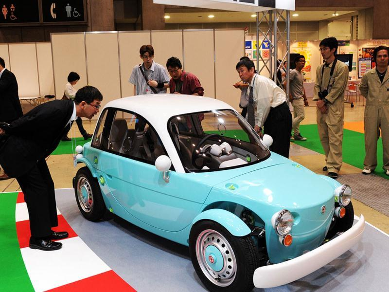Visitors admire Japanese auto giant Toyota Motor's concept model of a three-seater electric vehicle with toy-like design body