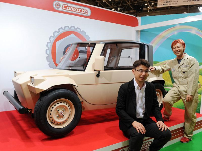 Japan's auto giant Toyota Motor engineer Kenji Tsuji (L) and car designer Kota Nezu display the concept model of a three-seater electric vehicle with toy-like design body