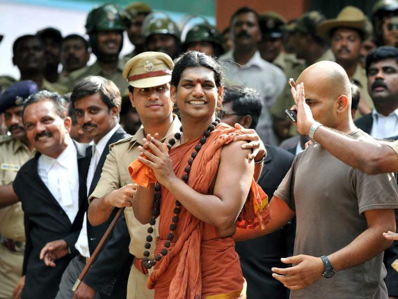 Police escort Godman Swami Nityananda (C) after appearing for his bail plea at the judicial magistrate court at Ramanagar District, some 50 kms from Bangalore. AFP Photo/Manjunath Kiran