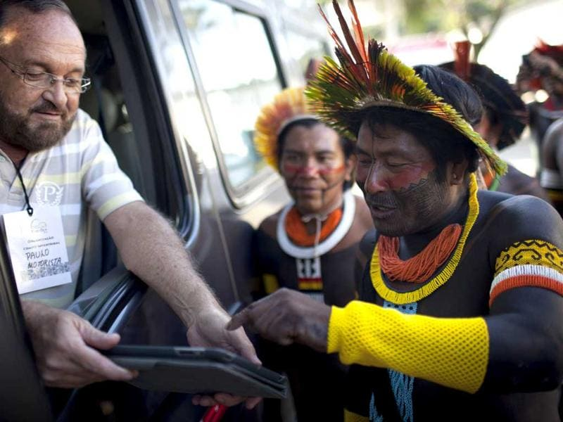 A van driver shows a tablet to members of the Caiapo tribe at the Kari-Oca village, during the United Nations Conference on Sustainable Development, or Rio+20, in Rio de Janeiro, Brazil,. The United Nations' largest-ever conference has kicked off in Rio de Janeiro. AP Photo/Felipe Dana