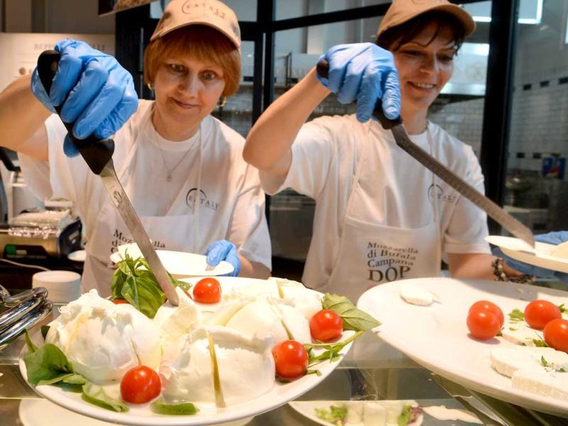 Employees serves mozzarella cheese at a counter of the Eataly food emporium in Rome. The huge 17000 square meter Italian food and wine market, which is part of the international