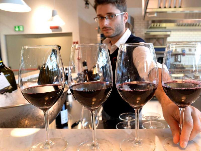 An employee serves Italian red wine at a counter of the Eataly food emporium in Rome. AFP Photo/Alberto Pizzoli