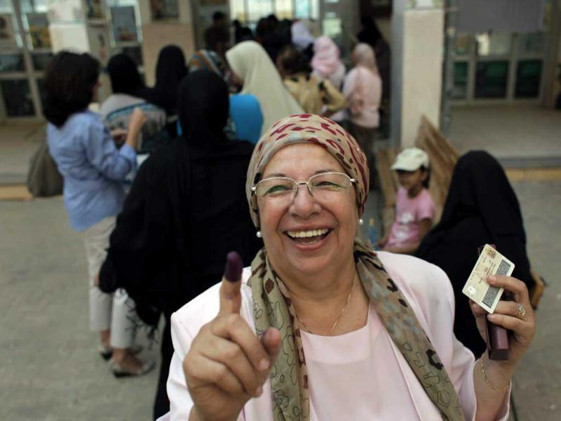An Egyptian woman shows her ink-stained finger after voting, while others line up in front of their polling station during the first day of the presidential runoff, in Cairo, Egypt. AP/Nasser Nasser