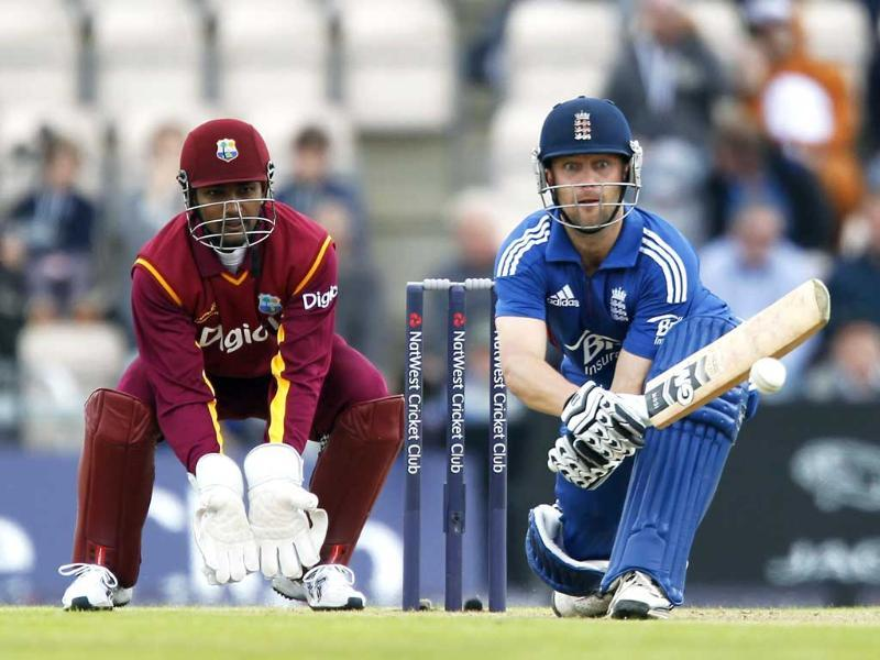 England's Jonathan Trott (R) plays a reverse sweep shot as West Indian wicketkeeper Denesh Ramdin looks on during their first ODI cricket match at The Ageas Bowl cricket ground in Southampton. AFP/Ian Kington