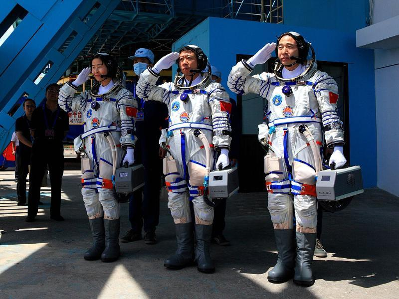 This picture shows Chinese People's Liberation Army (PLA) Air Force fighter pilot Liu Yang (L) together with her two male colleagues, Jing Haipeng (R) and Liu Wang (C), in their spacesuits as they pose at the Jiuquan space base, north China's Gansu province. AFP PHOTO
