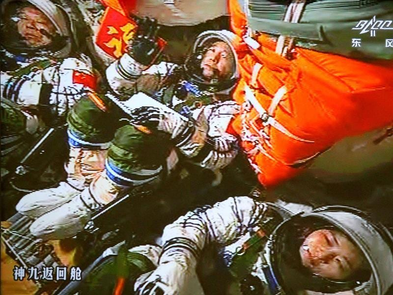 In this image made off the monitor screen at the Beijing Aerospace Flight Control Center and released by China's Xinhua News Agency, China's astronauts Jing Haipeng, center, Liu Wang, left, and Liu Yang sit inside the capsule after the launch of China's manned Shenzhou-9 spacecraft Shenzhou-9, atop an upgraded Long March-2F carrier rocket, blasted off from the Jiuquan Satellite Launch Center in northwestern China and accurately entered its orbit, Xinhua said. (AP Photo/Beijing Aerospace Flight Control Center via Xinhua)