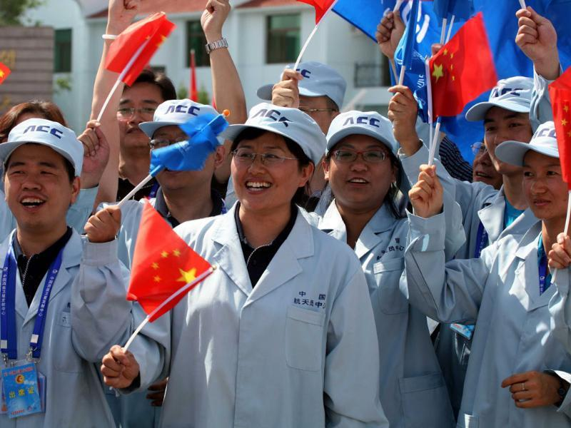 Chinese ground staff cheer as the astronauts make their way to board the Shenzhou-9 spacecraft, China's fourth manned space mission, which blasts off from the Jiuquan space base, northwest China's Gansu province in the remote Gobi desert. China launched its most ambitious space mission to date, sending its first female astronaut to the final frontier and bidding to achieve the country's first manual space docking. AFP PHOTO