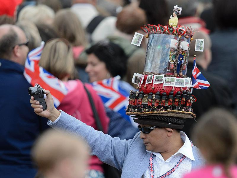 A royal supporter, wearing a hat made of models, stands outside Buckingham Palace following the Queen's Birthday Parade, 'Trooping the Colour' at Horse Guards Parade in London. AFP/Leon Neal