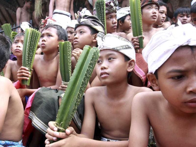 Balinese boys hold tied thorny pandanous leaves during Mekare Kare ritual in Teganan, Indonesia. Mekare Kare is the highlight of a local Hindu ceremony. AP/Firdia Lisnawati