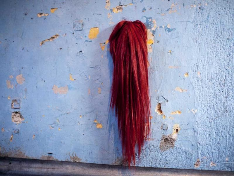 A wig hangs from a wall at the home where transgender contestants prepare to compete in the Miss Night Queen beauty pageant in Guatemala City. (AP Photo/Rodrigo Abd)