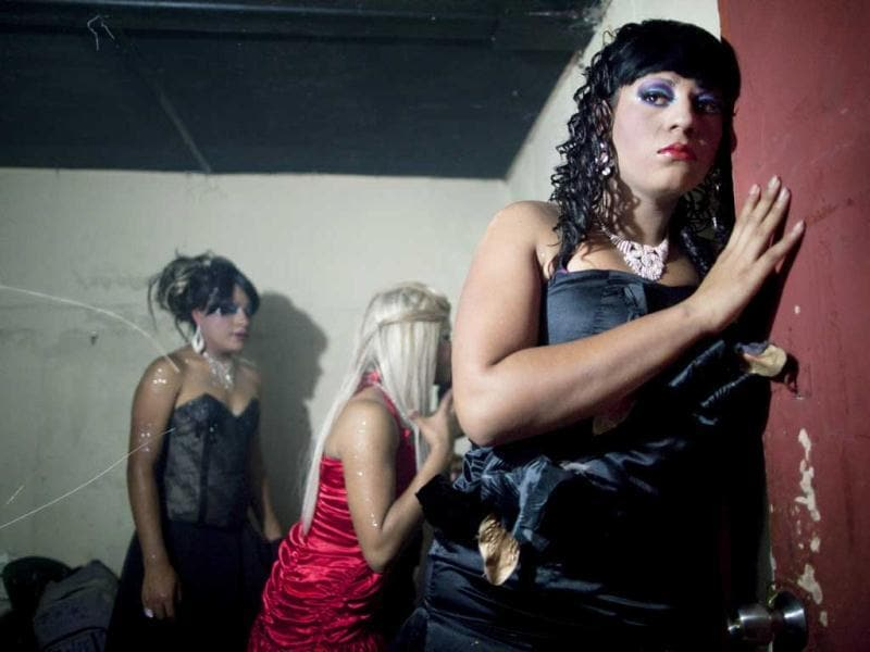 Contestant Erika watches her competitors perform in the Miss Night Queen beauty pageant from backstage in Guatemala City. The winner will represent the transgender community for one year. (AP Photo/Rodrigo Abd)