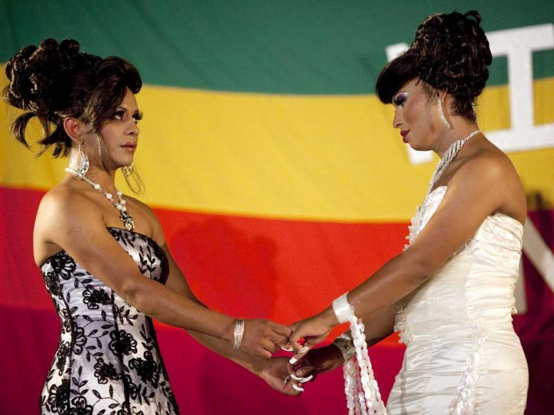 Miss Night Queen beauty pageant finalists Kendra Ferrari, 21, right, and Stefani, 21, hold hands as they wait for final announcement by judges in Guatemala City. Ferrari won the pageant and will represent the transgender community for one year. (AP Photo/Rodrigo Abd)