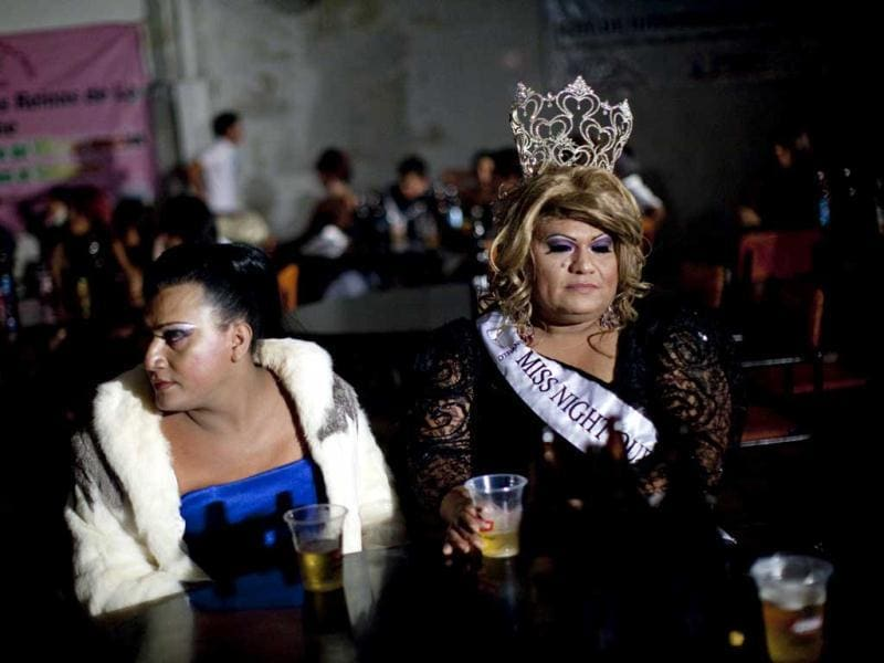 Miss Night Queen 2011, Dulce, right, drinks beer with a friend during the Miss Night Queen 2012 beauty pageant in Guatemala City. The winner will represent the transgender community for one year. (AP Photo/Rodrigo Abd)