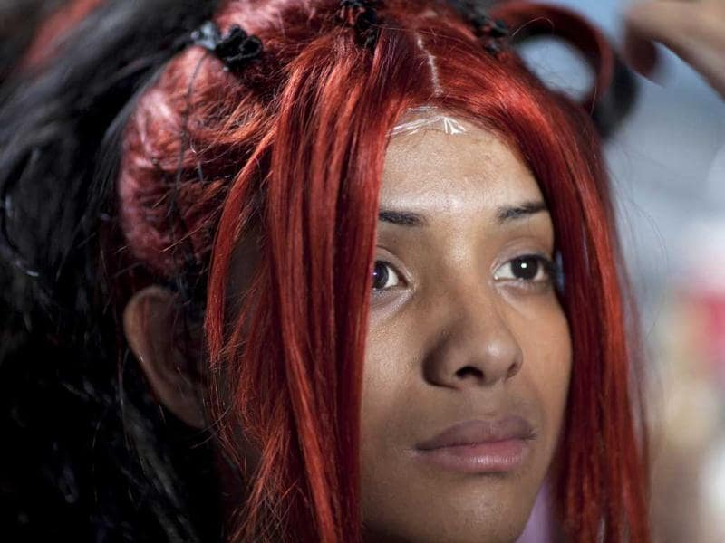 Transgender, Alondra, 17, waits for a friend to finish fixing her wig as she prepares to compete in the Miss Night Queen beauty pageant in Guatemala City. The winner will represent the transgender community for one year. (AP Photo/Rodrigo Abd)
