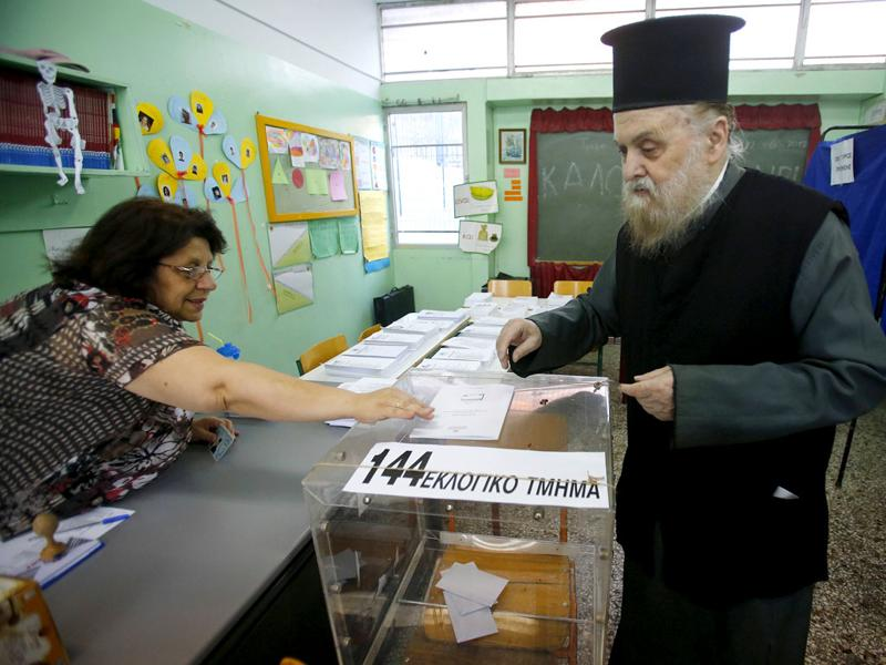 A Greek Orthodox priest casts his ballot at an Athens primary school used as a polling station. Voting opened on Sunday in a Greek election that could decide whether the heavily indebted country remains in the euro zone or heads for the exit, potentially unleashing shocks that could break up the single currency. REUTERS/Yannis Behrakis