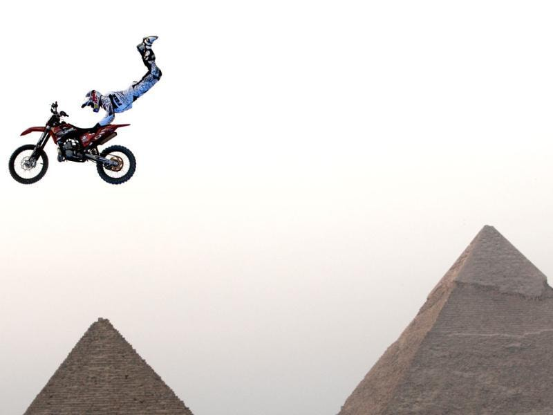 A biker performs in front of the Great Giza pyramids during Red Bull Fighters International Freestyle Motocross Exhibition Tour on the outskirts of Cairo. REUTERS/Goran Tomasevic