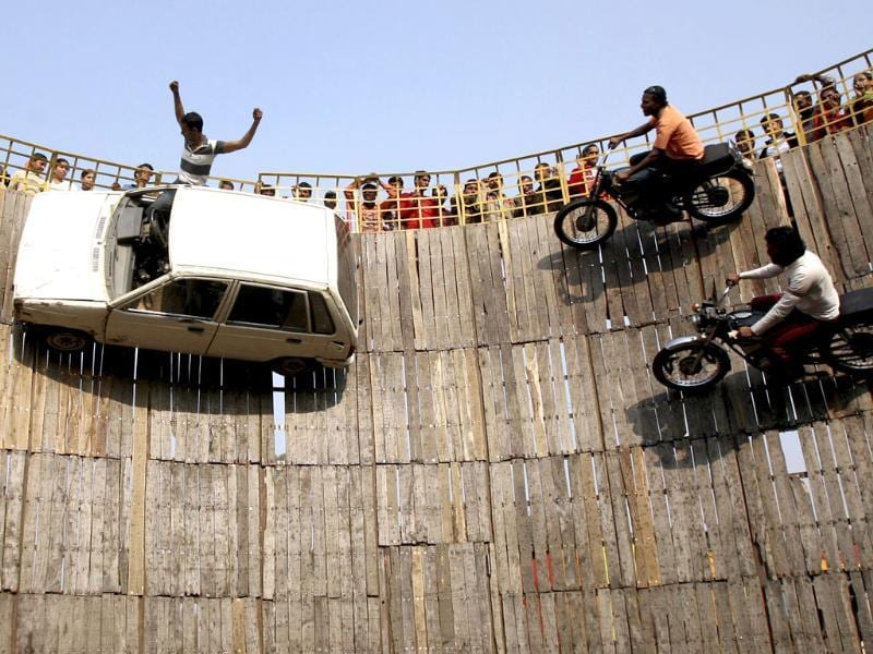 Stuntmen perform on their motorbikes and car on the walls of the