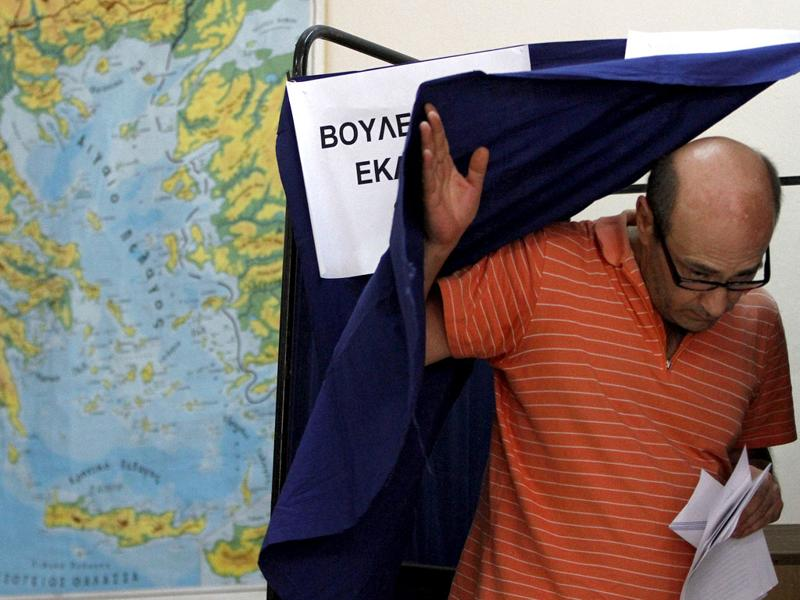 A Greek man leaves the booth after voting during the elections in Athens. AP Photo/Petros Karadjias