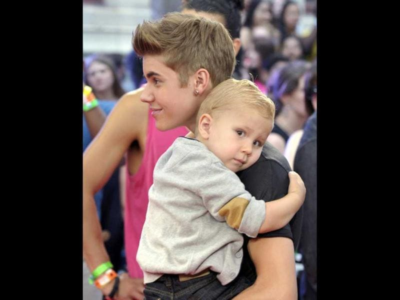 Performer Justin Bieber carries his younger brother Jaxon as he arrives for the MuchMusic Video Awards in Toronto. Reuters/Mike Cassese