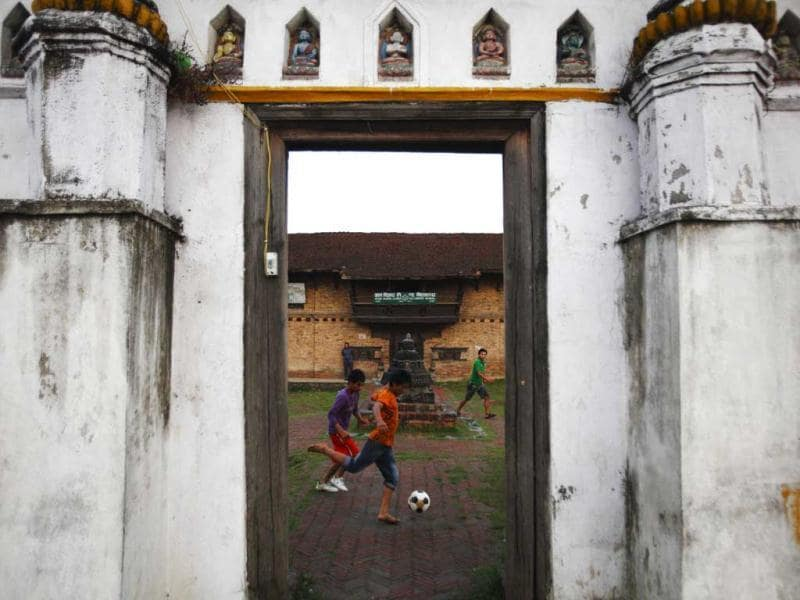 Boys playing soccer are pictured through the door of a temple at the ancient city of Bhaktapur, near Kathmandu. Reuters photo/Navesh Chitrakar