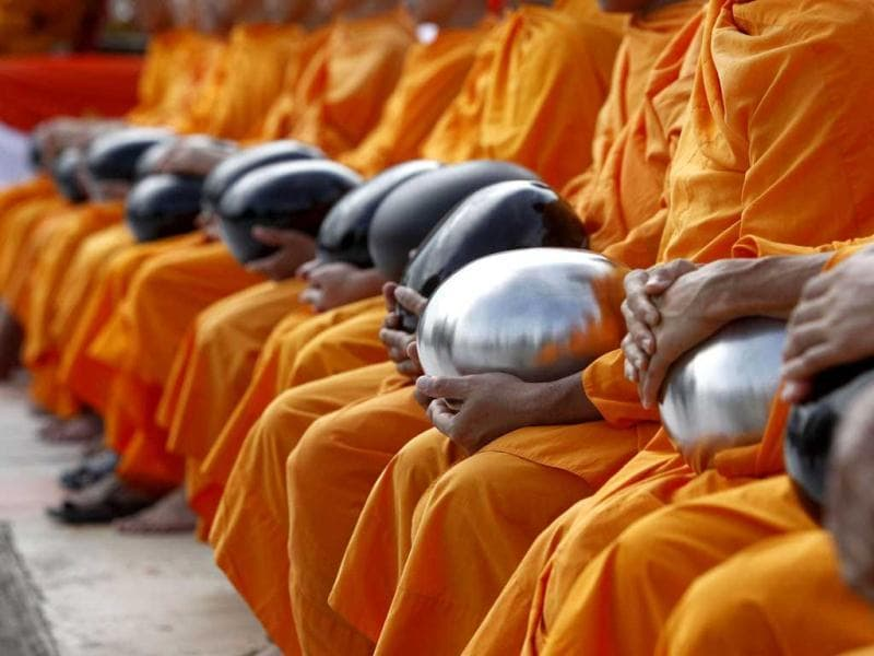 Buddhist monks sit wait for a mass alms-offering ceremony at King Mongkut's Institute of Technology Ladkrabang in Bangkok. Reuters photo/Sukree Sukplang