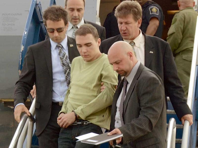 In this photo provided by Montreal Police, Luka Rocco Magnotta is taken by police from a Canadian military plane to a waiting van in Mirabel, Quebec. Magnotta, the suspect in the killing and dismemberment of a Chinese student, returned to Canada via military transport from Germany, where he was arrested this month. AP photo/Montreal Police