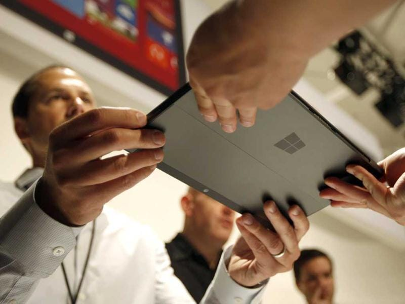 A Microsoft representative (L) hands the new Surface to a member of the press as it is unveiled by Microsoft. Reuters/David McNew